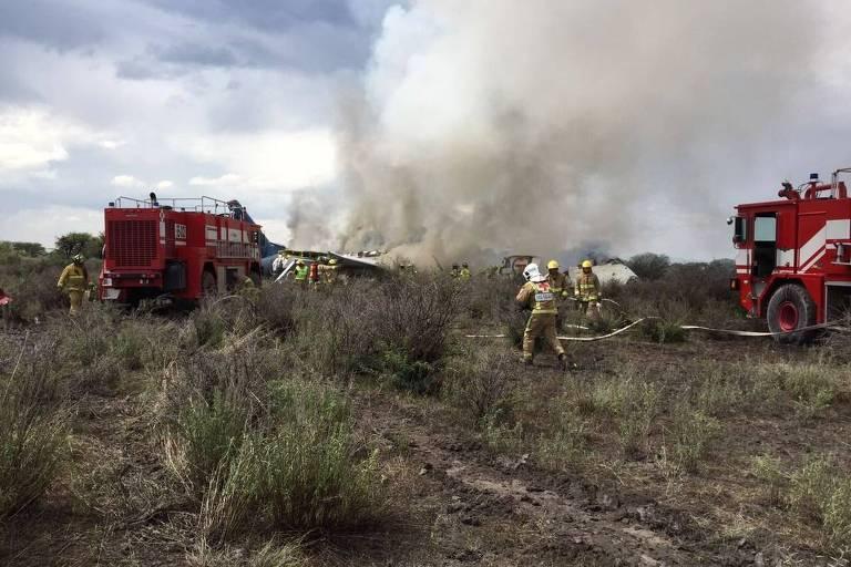 Caminhões de combate ao fogo e bombeiros com roupas de cor amarela se aproximam de uma área de fumaça branca em que se pode ver parte da fuselagem de um avião.