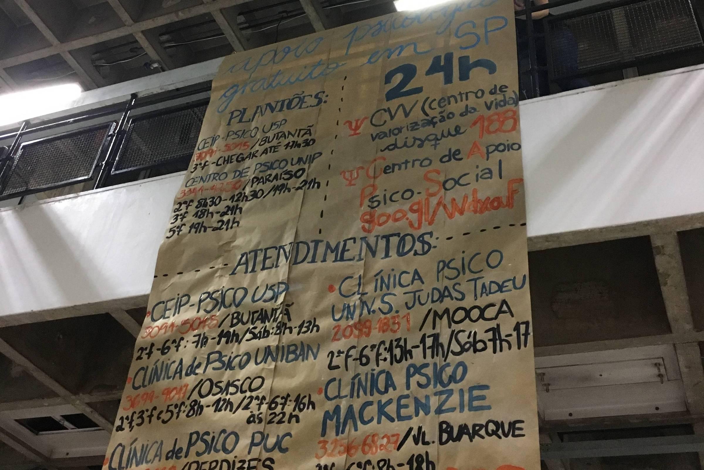 Cartaz de papel craft marron pendurado do primeiro andar da faculdade de ciências sociais da USP mostra, em letras coloridas pintadas com tinta guache, uma lista de serviços de saúde mental e prevenção ao suicídio disponíveis gratuitamente para estudantes