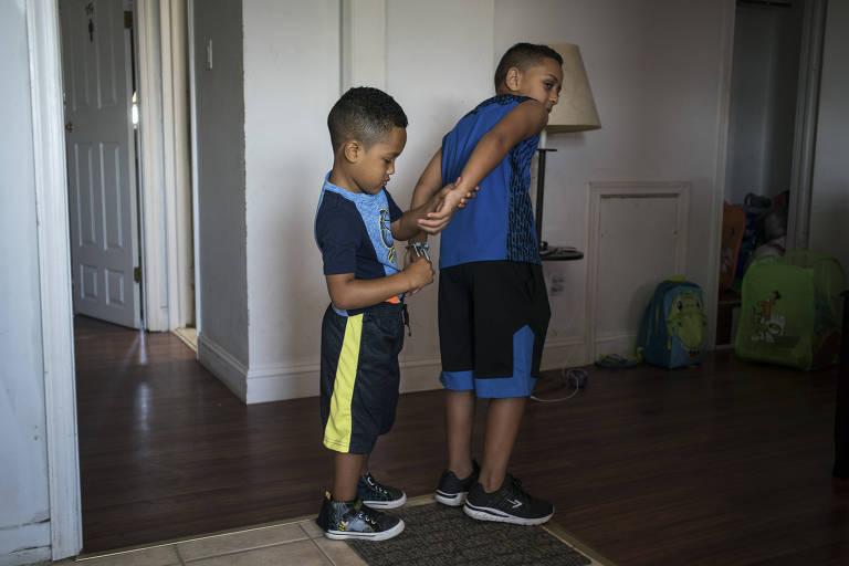 Thiago está com uma bermuda preta com listra branca e segura as mãos do primo, que as junta de costas