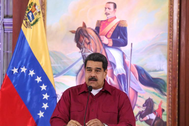 De camisa vermelha, Maduro aparece falando em um microfone de mesa sentado, com a bandeira da Venezuela à sua esquerda e o retrato de um dos próceres venezuelanos atrás