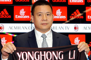 FILE PHOTO: Yonghong Li shows a AC Milan jersey during a news conference in Milan