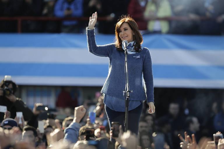 De casaco azul e calça jeans e de pé diante de um microfone, Cristina acena de um palco central para seus seguidores, que aparecem abaixo gravando a cena com celulares. Ao fundo, a divisão das arquibancadas do estádio onde ela fala tem uma faixa com as cores da bandeira argentina.