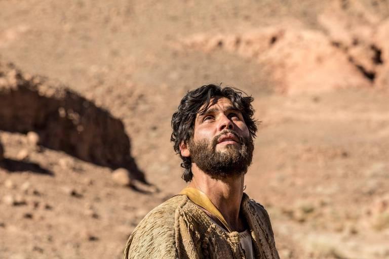 O ator Dudu Azevedo, como o protagonista da novela Jesus, olha para cima no meio do deserto e clima ensolarado.