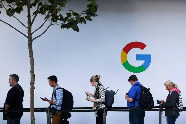 Fila de pessoas mexendo no celular em frente a um painel branco com o logo do Google