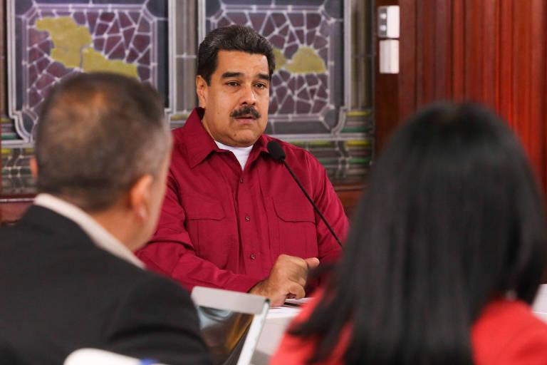 Maduro aparece entre as cabeças (de costas) de dois de seus aliados: à esquerda o ministro Tareck el-Aissami e à direita, sua vice, Delcy Rodríguez