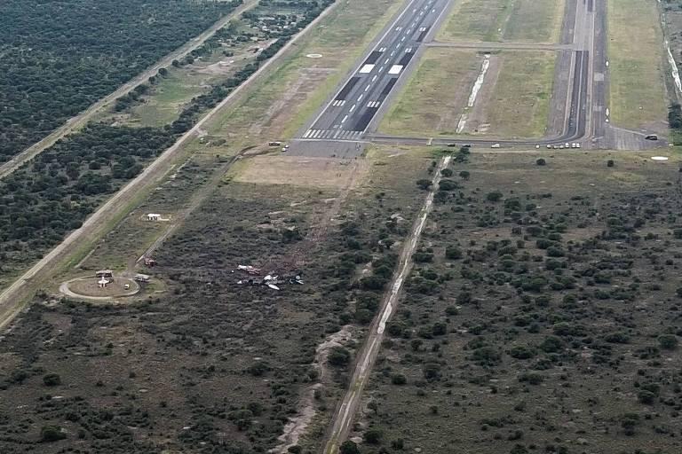 Destroços do avião aparecem em meio à mata pouco depois da pista do lado esquerdo. Há uma segunda pista que aparece do lado direito.