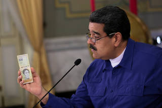 Venezuela's President Nicolas Maduro holds a bank note of the new Venezuela's currency Bolivar Soberano (Sovereign Bolivar) as he speaks during a meeting with ministers at Miraflores Palace in Caracas