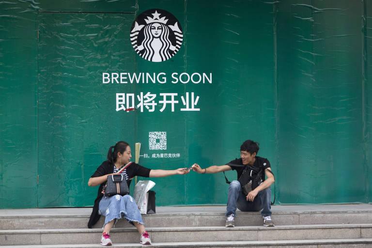Homem e mulher sentados em frente ao aviso de uma loja do Starbucks