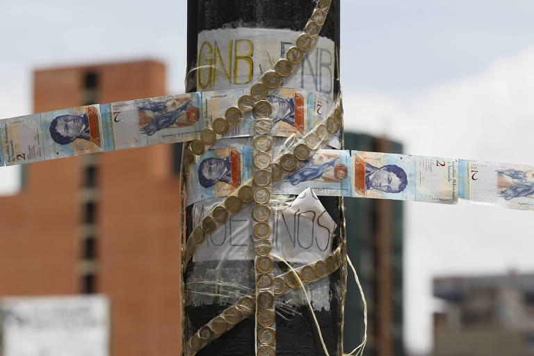Notas de bolívar e moedas são vistas enroladas em um poste. Ao fundo, aparecem três prédios altos de Caracas.