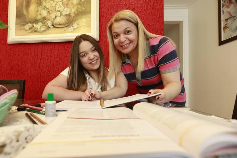A mãe, Silene, com sua filha, Julia, seguram canetas e cadernos para estudarem para as provas