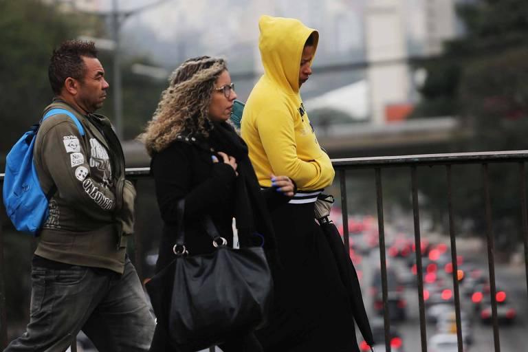 Pedestres se protegem do frio no viaduto Santa Generosa, no Paraíso, em São Paulo (SP)