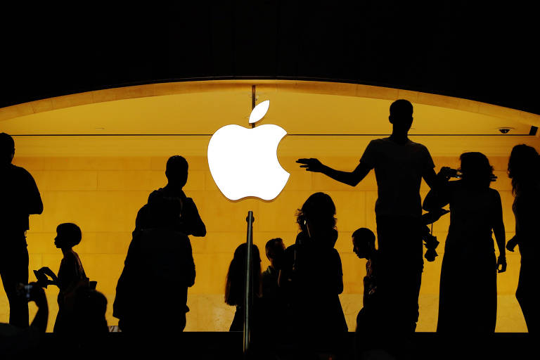Clientes caminham em frente ao logo da Apple, em loja da marca em Nova York