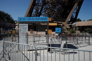 A sign announcing the closure of the Eiffel Tower is seen at a closed ticket sales counter as part of a strike by employees over lengthening queues during the peak summer tourist season in Paris