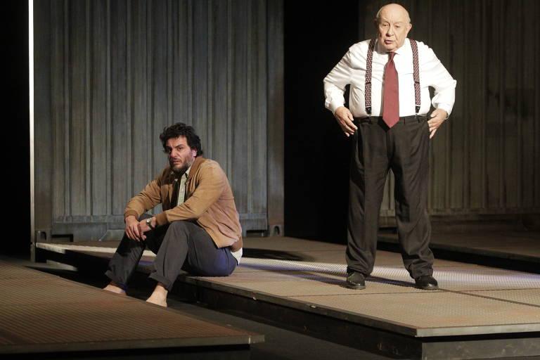 um homem sentado e outro, mas velho, em pé em palco