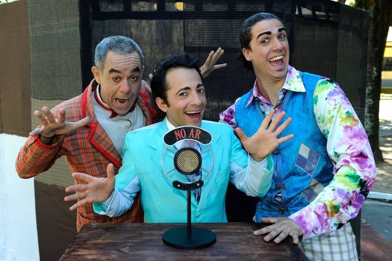 Três palhaços com um microfone vintage