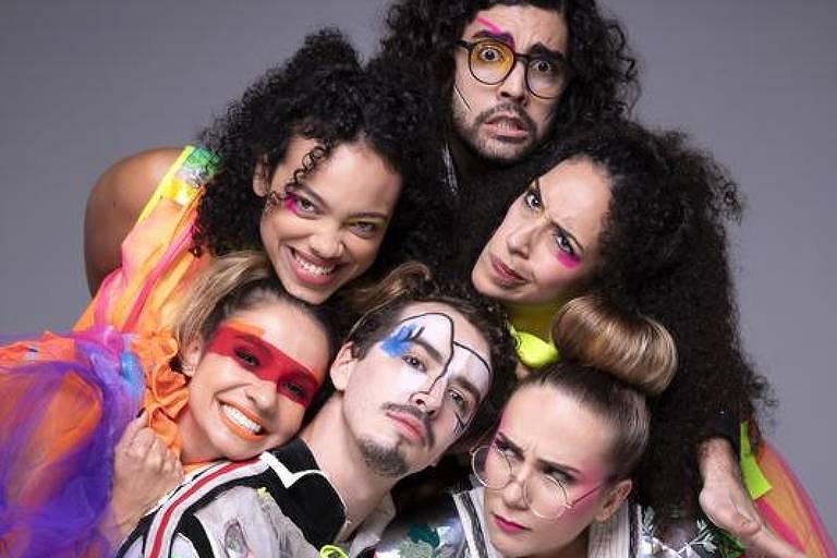 Seis atores de teatro com roupas coloridas