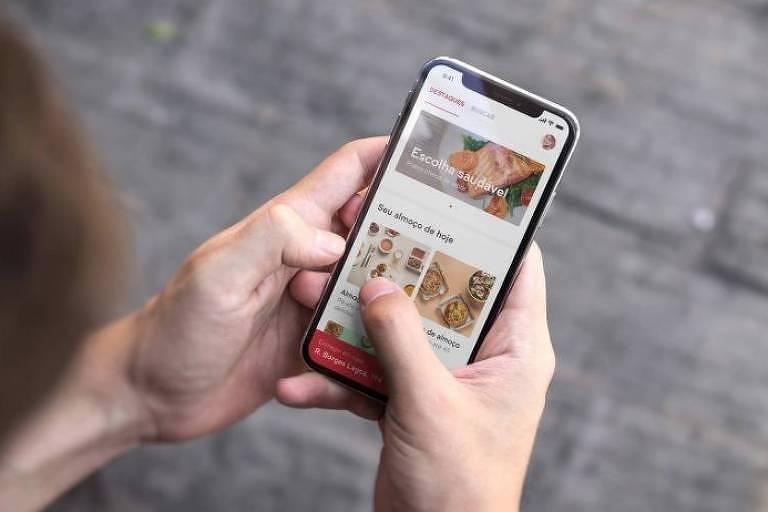 Pessoa manuseia celular que está no aplicativo ifood