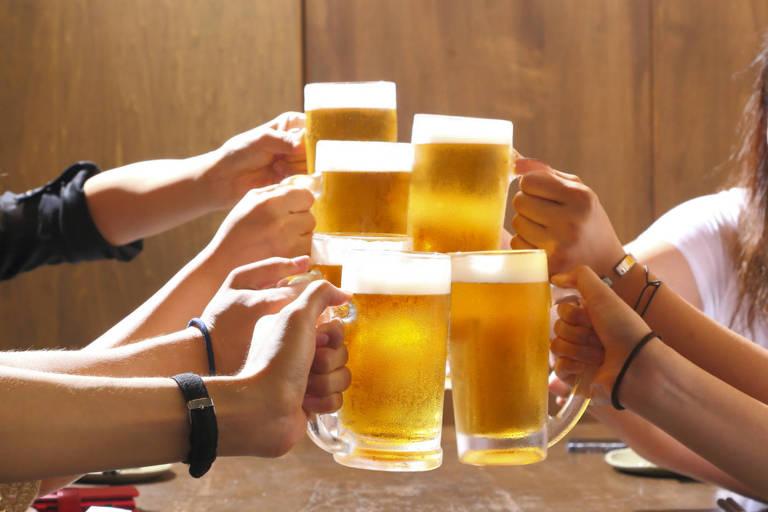 Mãos seguram caneca com cerveja e fazem brinde