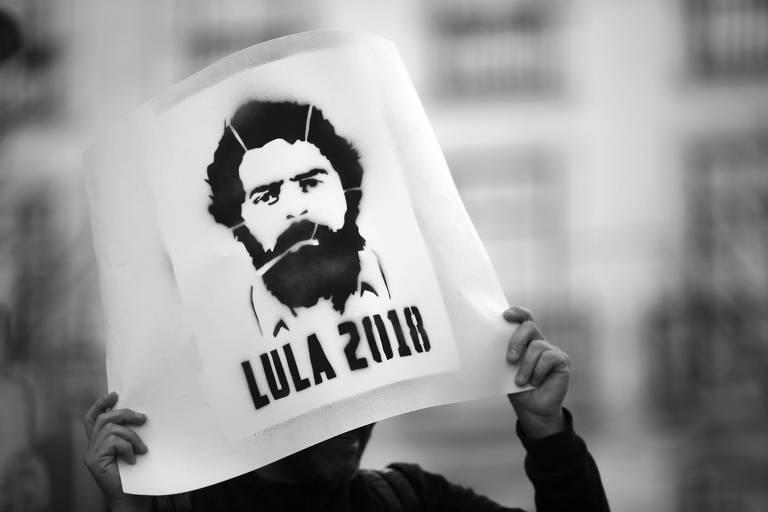Manifestante segura cartaz com imagem de Lula durante protesto a favor do ex-presidente, em abril, em Lisboa