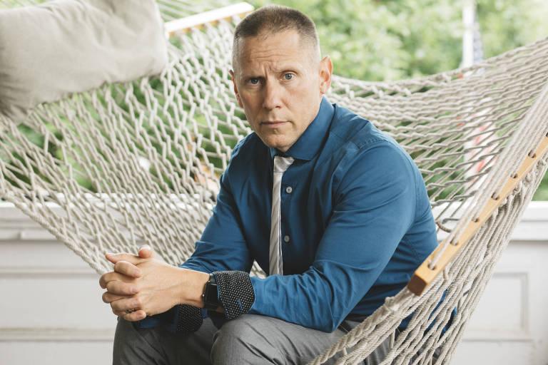 Vestido com calça cinza e camisa azul escura, Snyder-Hill aparece sentado em uma cadeira de rede.
