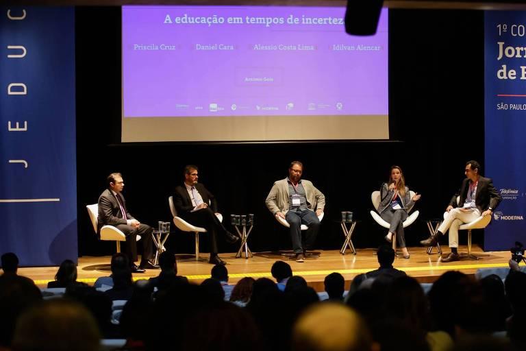 Cinco pessoas sentadas no palco de um auditório