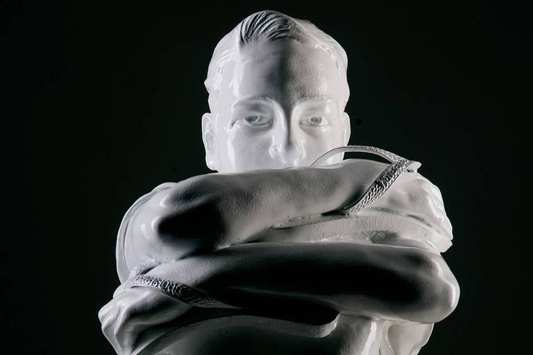 escultura de homem branco com braços em volta de si