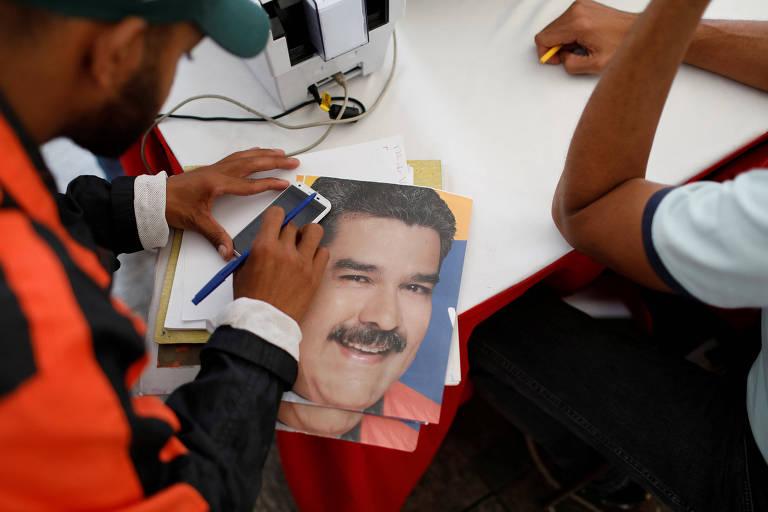 Folhetos estão em cima da mesa. Em cima de um deles um homem que veste casaco preto e laranja apoia um celular e um bloco de papel. Ao lado, aparece o braço de outra pessoa de camiseta branca.