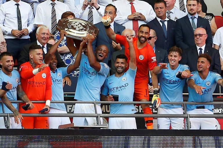 O capitão Kompany, do Manchester City, levanta a taça da Supercopa da Inglaterra, tendo ao lado os brasileiros Fernandinho e o goleiro Ederson (à esquerda)