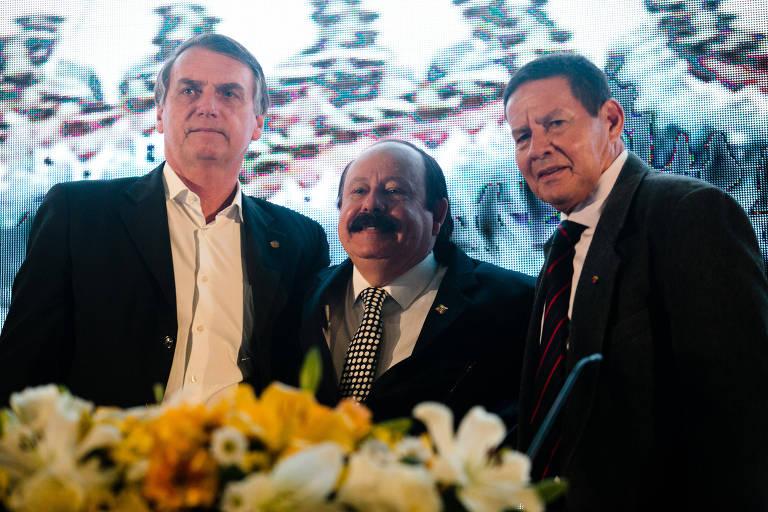 Bolsonaro, Levy Fidelix e o general Hamilton Mourão na convenção do PRTB, em São Paulo. Eles estão de terno e gravata, exceto Bolsonaro - que está sem o acessório.