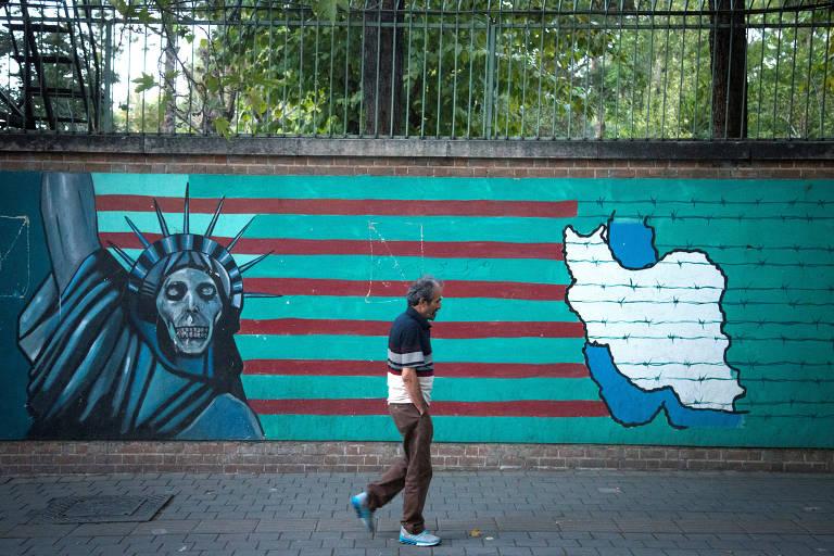 Homem caminha em frente a muro antiamericano em Teerã, no Irã