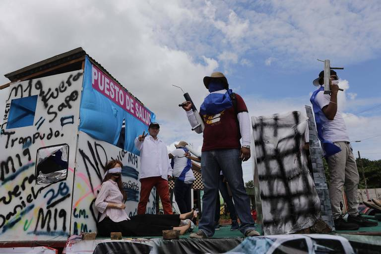 Três homens encapuzados empunhando rojões e armas improvisadas sobem em um carro no meio de uma rua em Manágua
