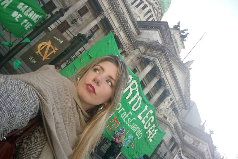 Freijo aparece em frente ao Congresso da Argentina. Atrás dela faixas verdes pelo aborto legal.