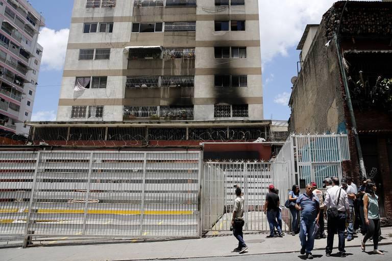 Grupo de pessoas está na frente do portão. O prédio aparece com a fachada e as janelas dos três primeiros andares escurecidas devido ao incêndio.
