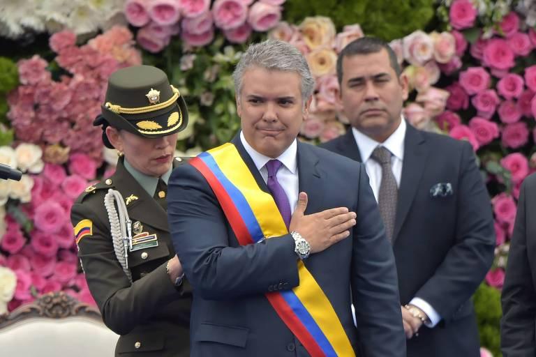 Com terno cinza, camisa branca e gravata lilás, Duque coloca a mão no peito após receber a faixa presidencial colombiana. Uma soldado faz ajustes na faixa. Ao fundo, arranjos florais enfeitam o palco.