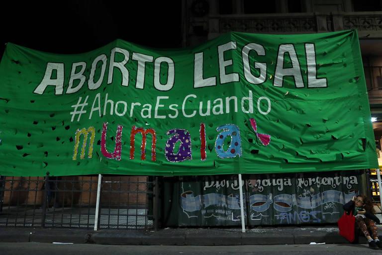 """A mulher está sentada no chão, abaixo da faixa de cor verde que diz: """"Aborto legal: agora é quando"""""""