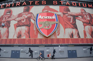 People walk and cycle past Emirates Stadium, the home of Arsenal soccer club in London, Britain