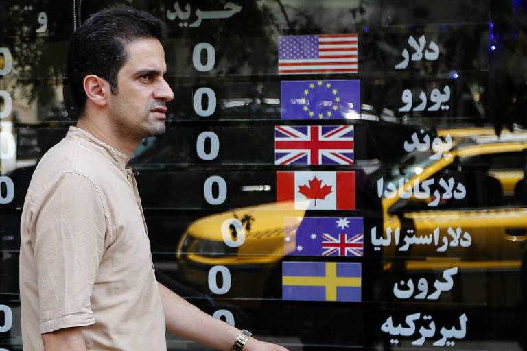 Iraniano passa em frente a casa de câmbio em Teerã nesta quarta-feira (8), um dia após a reimposição de sanções americanas contra o Irã