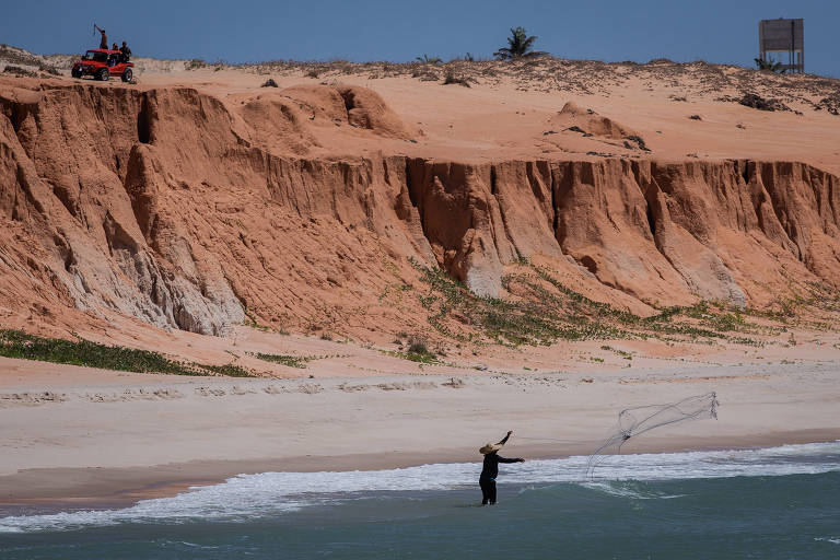Pescador joga rede ao mar na praia de Canoa Quebrada, no município de Aracati, no Ceará