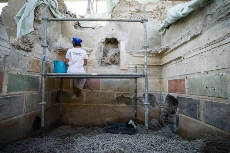 Pesquisadora em cima de andaima dentro de cômodo de antiga casa em Pompeia