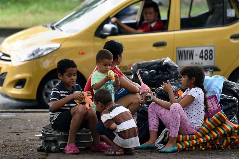 As cinco crianças estão sentadas em malas que estão em uma calçada de terra. Um táxi amarelo de Cali passa ao lado do grupo.