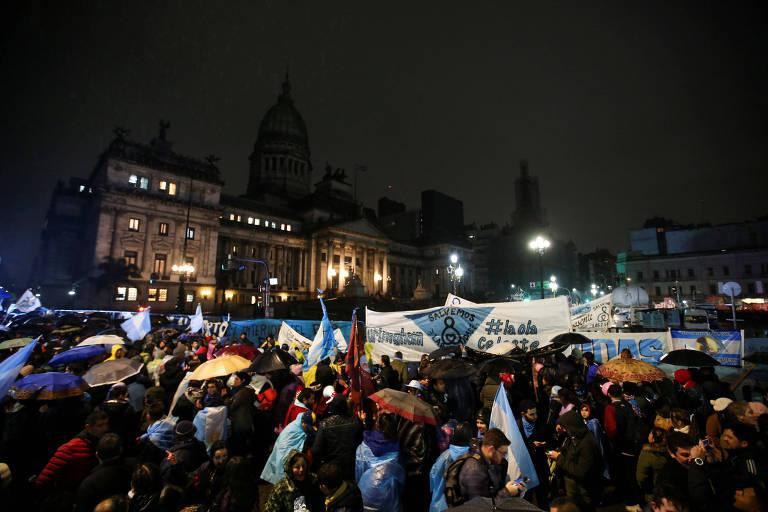Manifestantes seguram faixas azuis celestes e bandeiras da Argentina. Ao fundo, vê-se o Congresso argentino.