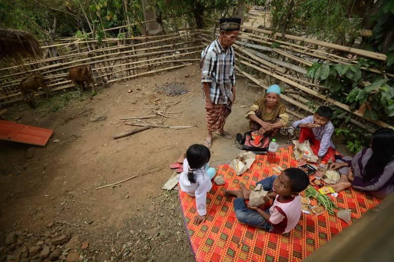 Família faz refeição sentada no chão dentro de sua casa destruída por terremoto