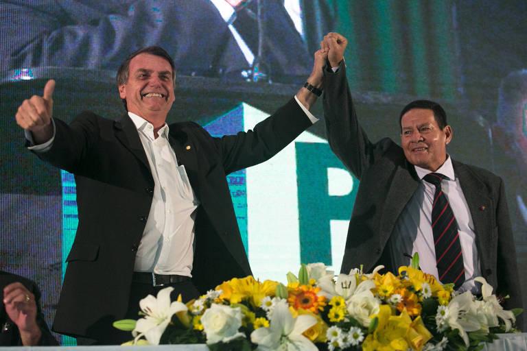 Jair Bolsonaro de braço erguido com Hamilton Mourão
