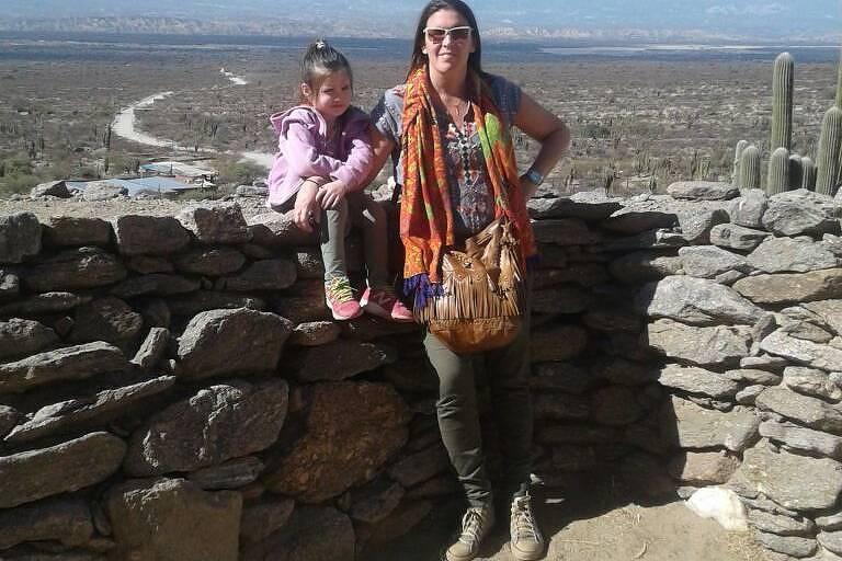Mariana Ravazzola posa com sua filha de quatro anos em um muro