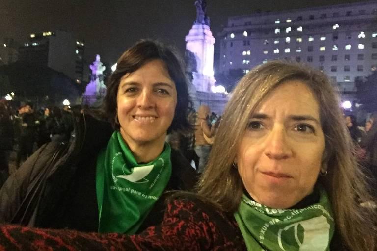 Ana Correa ao lado de Ingrid Beck em uma marcha pró-aborto à noite