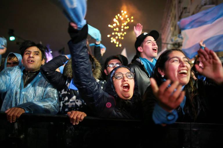 Grupo de dez pessoas levanta panos de cor azul celeste e bandeiras da Argentina. Ao fundo no céu, é possível ver fogos de artifício estourando.