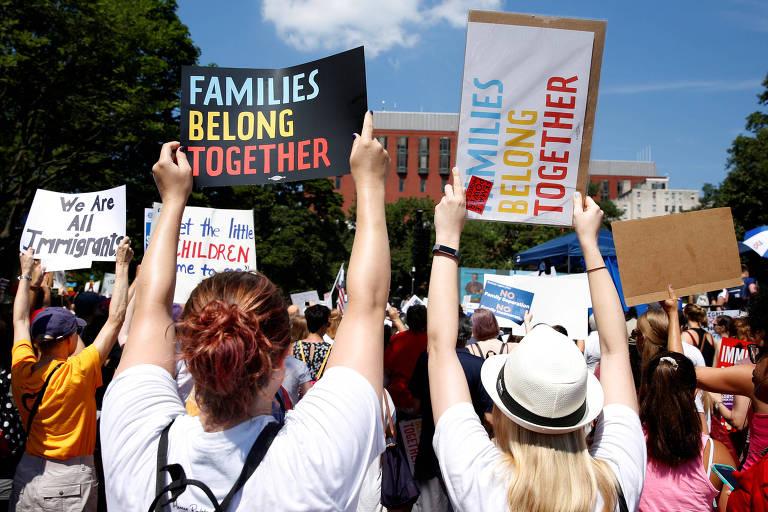 """Grupo de dez pessoas aparece de costas, algumas delas carregando cartazes com a mensagem: """"As famílias devem permanecer juntas"""""""
