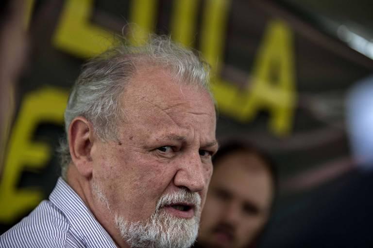 """Foto mostra João Pedro Stédile, um dos principais líderes do MST, olhando de lado. Ele está de camisa com listras azul e branca. Atrás dele, está o nome """"Lula"""" em letras grandes, em amarelo e fundo preto"""