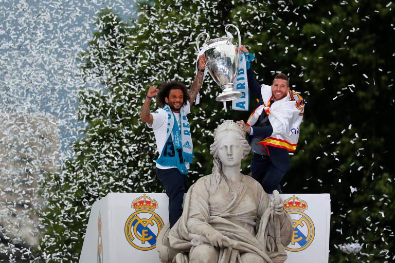 Marcelo e Sergio Ramos, jogadores do Real Madrid, levantam a taça da Liga dos Campeões no meio de uma chuva de papel picado