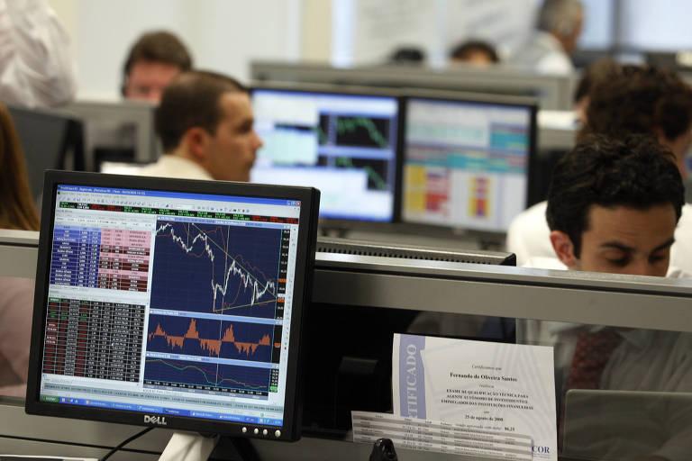 Operadores da  XP Investimentos, acompanham fechamento da bolsa de valores
